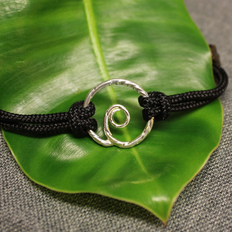Adjustable black nylon cord bracelet with sterling silver spiral in center.