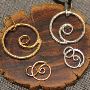 Small and larger sterling silver and 14k gold spiral pendants.