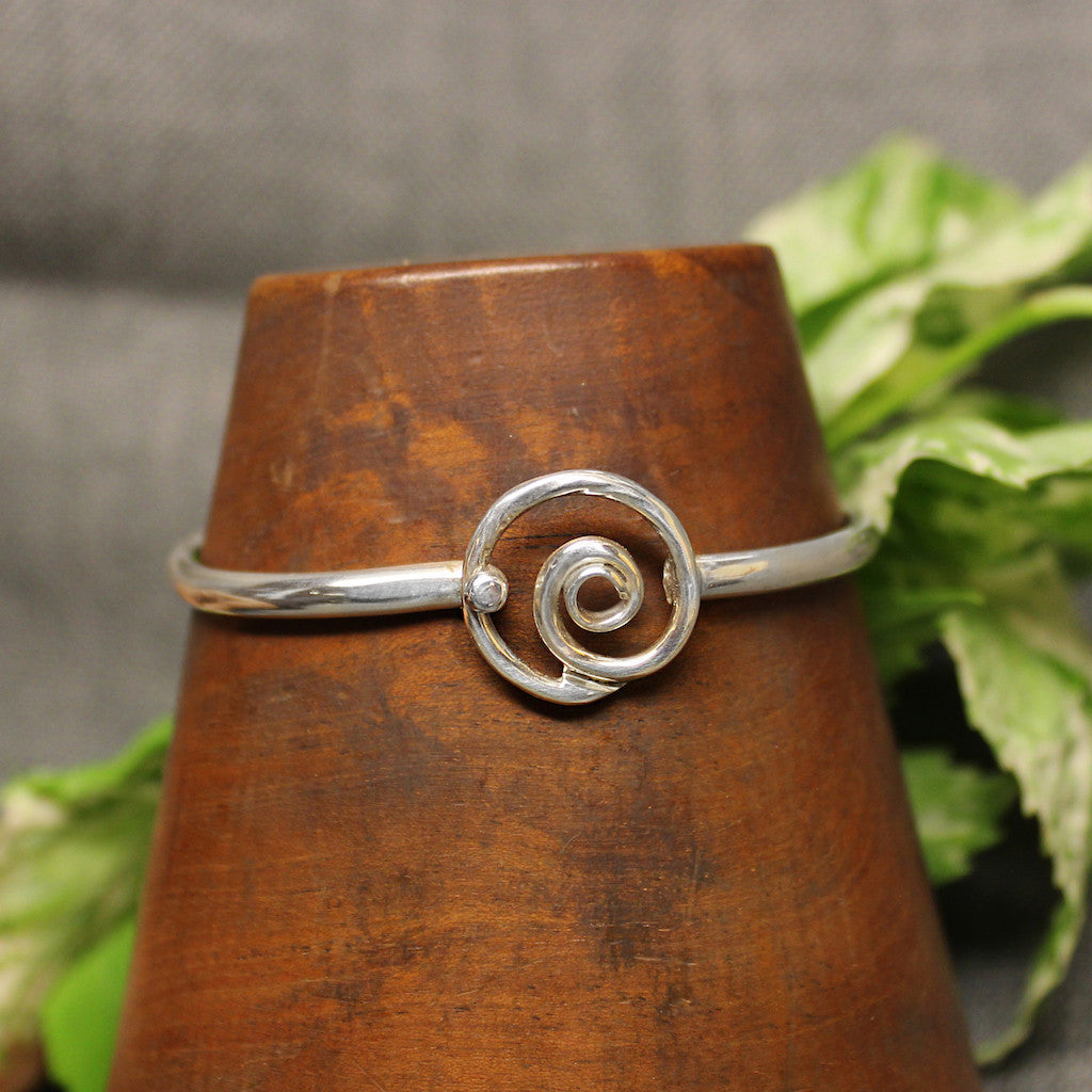 Thin sterling silver child's bracelet with spiral design in center.