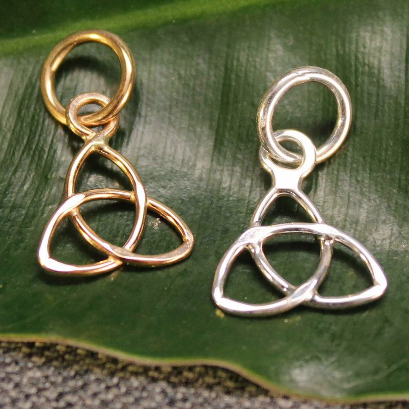 Sterling silver and 14k gold Trinity Knot charms.