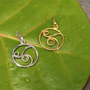 Circular 14k gold and sterling silver pendants with delicate rolling wave design in center.