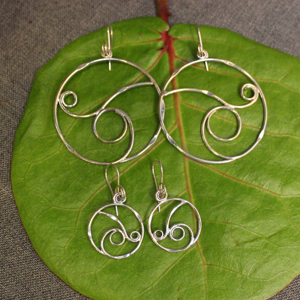 Small and large sterling silver hoop earrings with delicate rolling wave design in center.