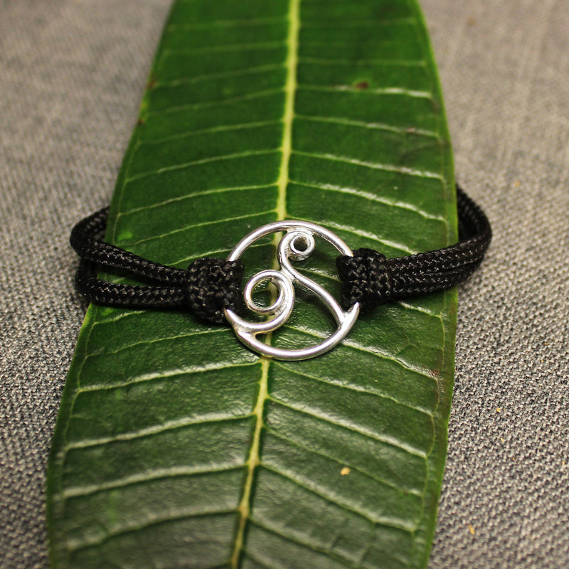 Adjustable black nylon cord bracelet with sterling silver circular design in center containing a delicate rolling wave.