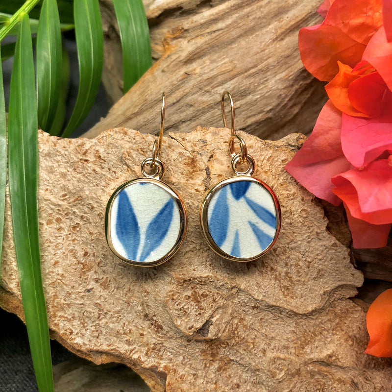 14k gold earrings with round Chaney inlay with white and blue leaf motif.