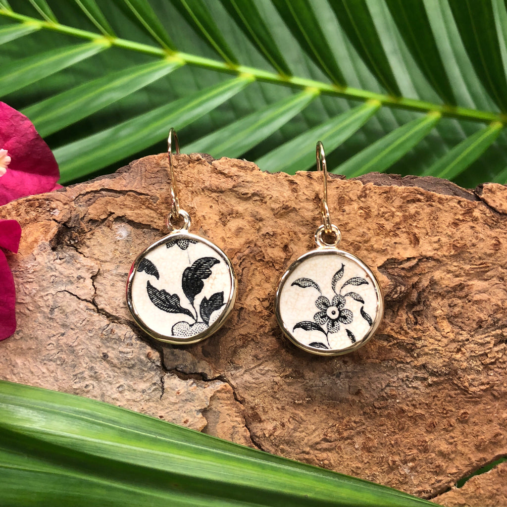 !4k gold drop earrings with round Chaney inlay with brown flower and leaf motif on white background.