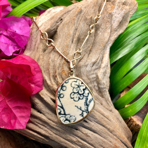 Large oblong-shaped 14k gold pendant with cream and navy floral design Chaney inlay.