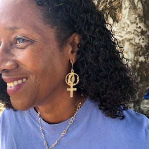 Woman wearing 14k gold earrings with Women's Coalition venus symbol.