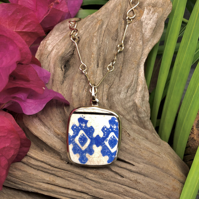 14k gold rectangular-shaped pendant with white Chaney piece with bright blue aztec design