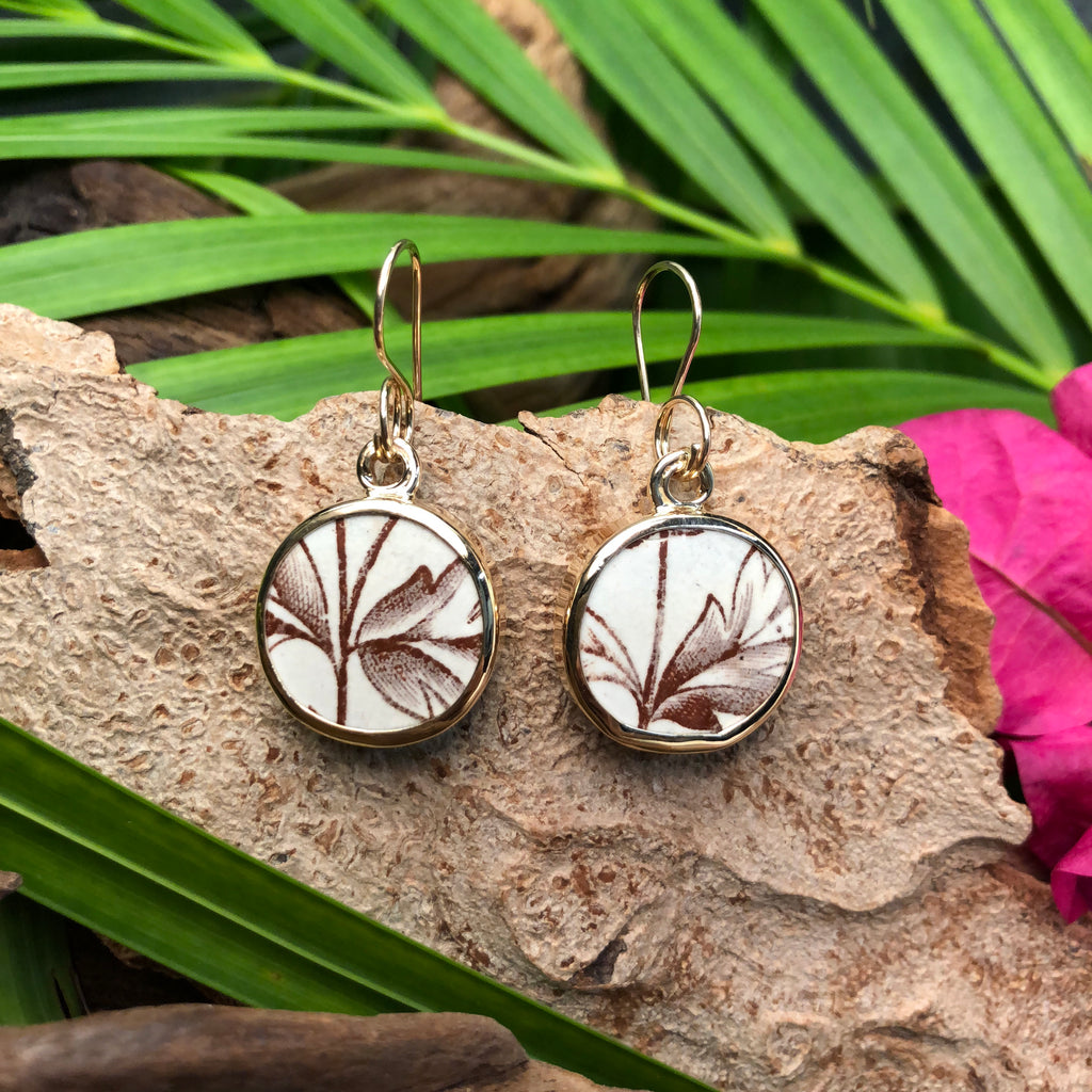 Round 14k gold earrings with white and brown Chaney inlay and floral motif.