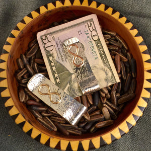 Hammered sterling silver money clip with 14k gold or copper infinity symbol in center.