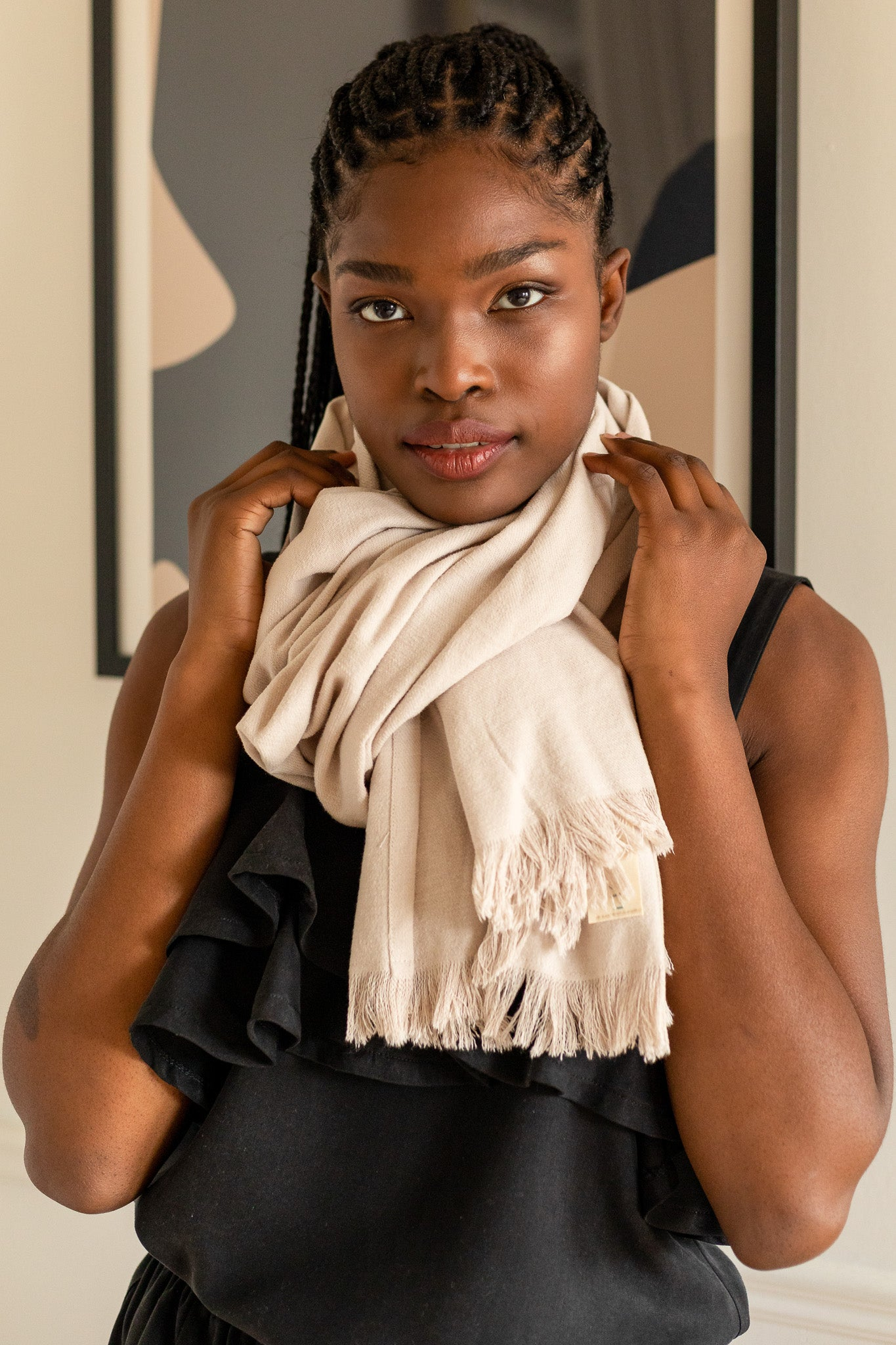 woman wearing all black except a winer white scarf tied around her neck