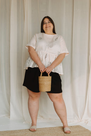 black linen shorts worn with shell print top and straw bucket bag