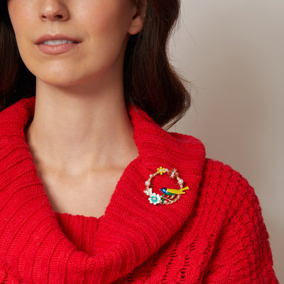 vintage brooch with bird in enamel worn on red jumper