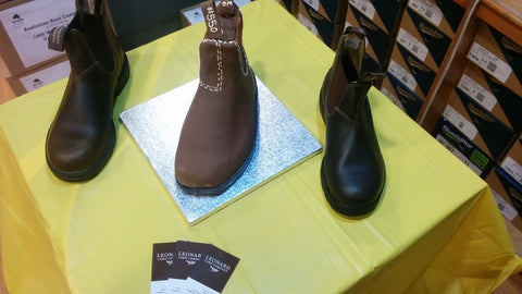 Two real Blundstone Boots beside a chocolate cake shaped like a Blundstone Boot