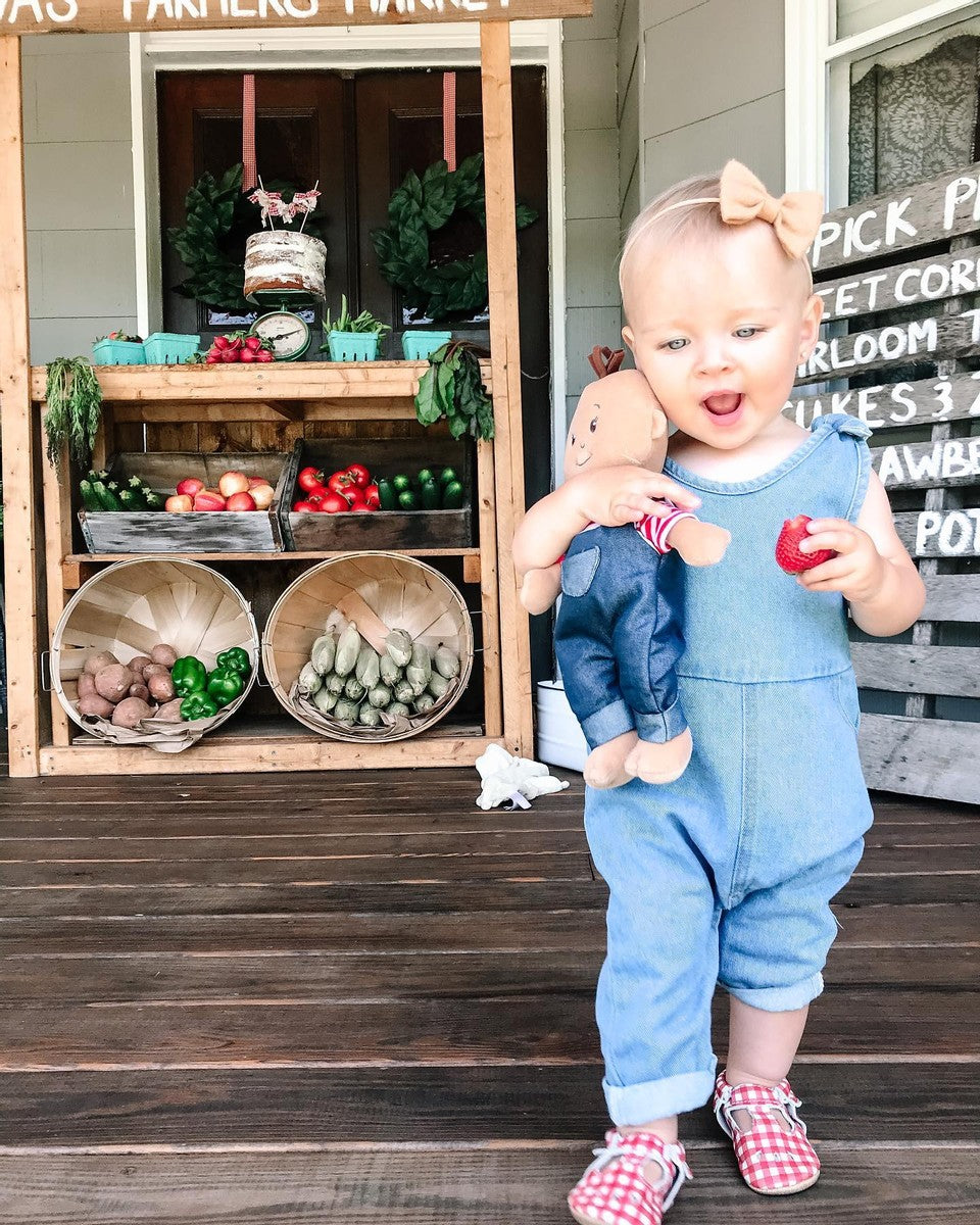 Toddler-age girl on porch with Wee Baby Stella farmer doll in hand and farmer's market stand behind her.