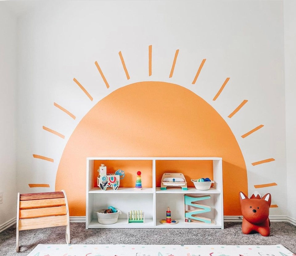 Play room scene with a bright orange sun on the wall, and a shelf full of toys from Manhattan Toy and other brands.