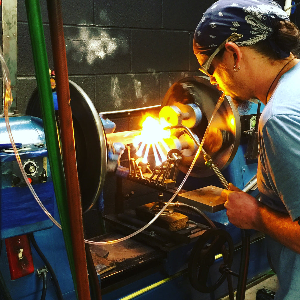 Peltcraft blowing glasss on the lathe at Green Flash Glass