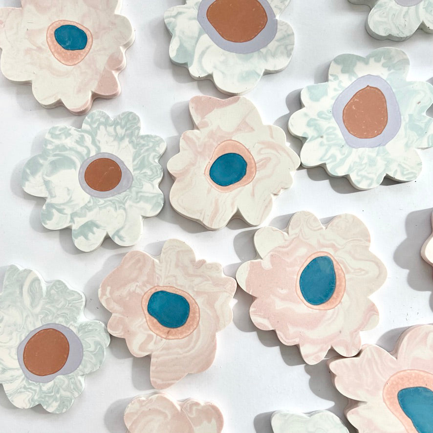 A variety of marbled Jesmonite flower-shaped coasters made with custom molds