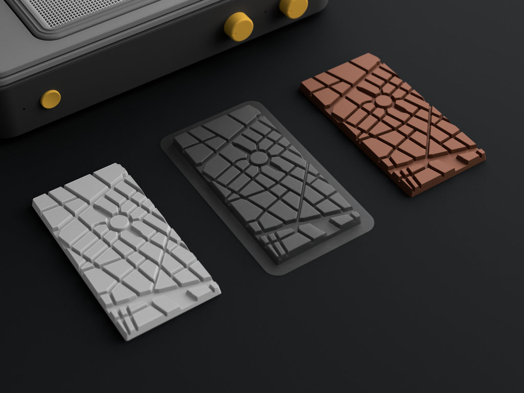 3D printed custom chocolate bar mold template and vacuum-formed mold on a table with a custom chocolate bar