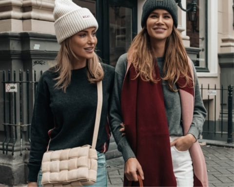 two girls with KCST beanies and scarves walking through Amsterdam streets