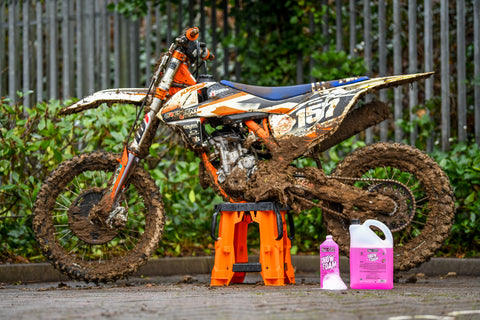 Dirty motocross bike with snow foam in foreground