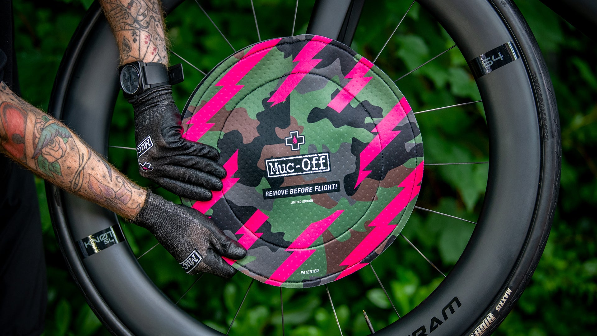 man fitting the camo disc brake cover to a bike