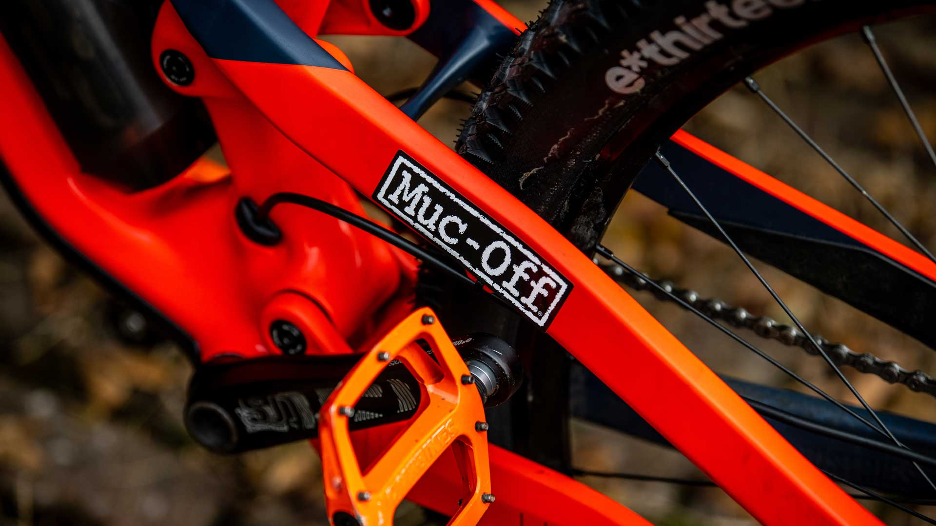 Muc-off black and white sticker stuck on orange bike frame