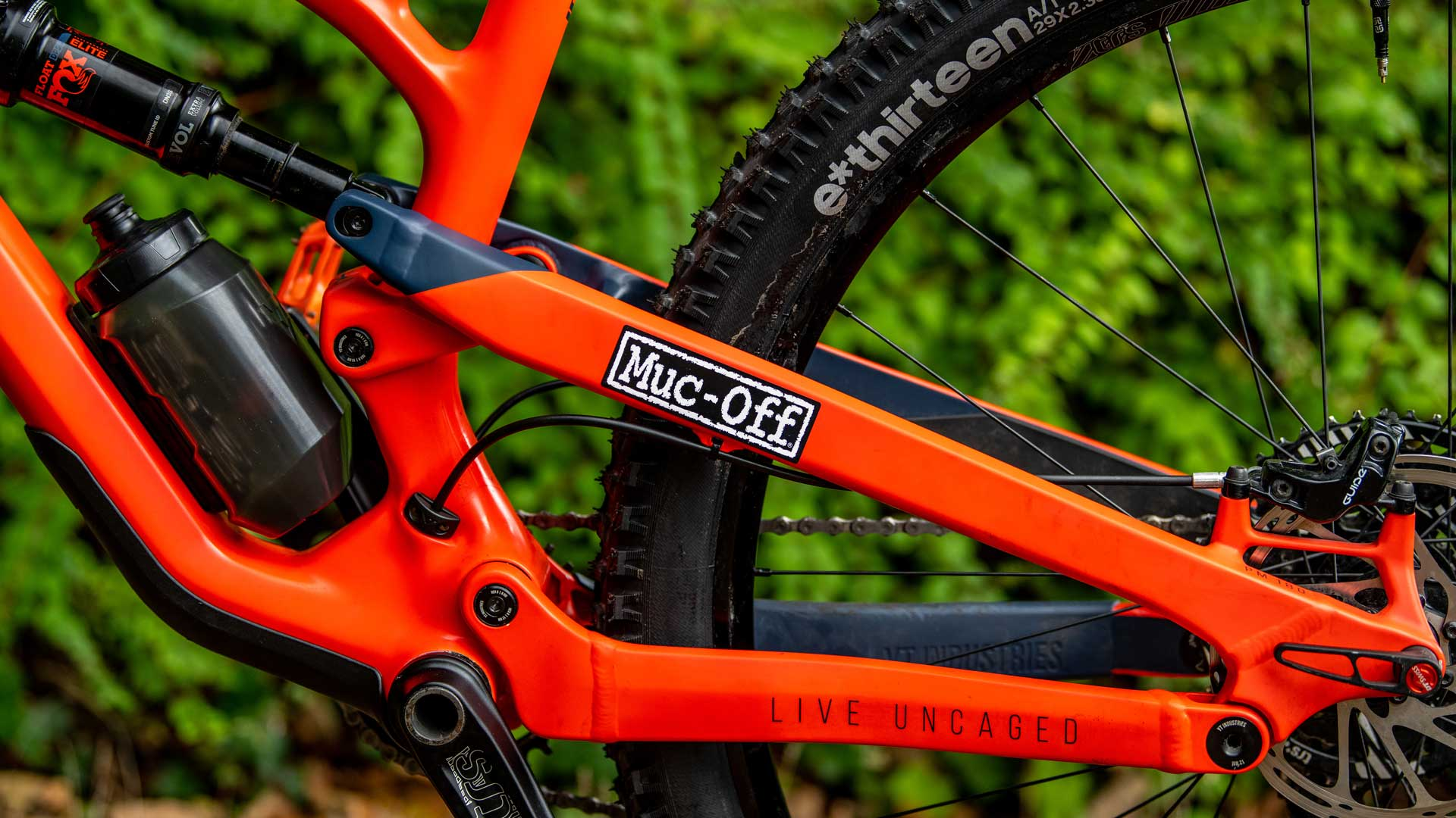 Black and white muc-off sticker on orange bike frame