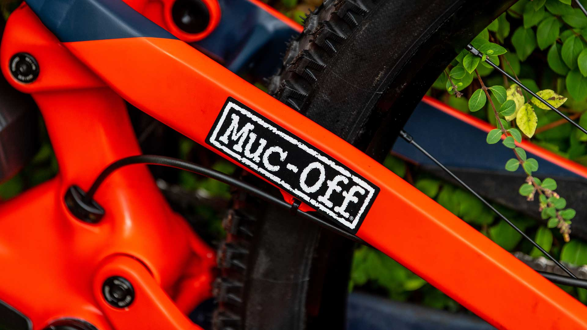 Close up of muc-off sticker stuck to an orange bike frame