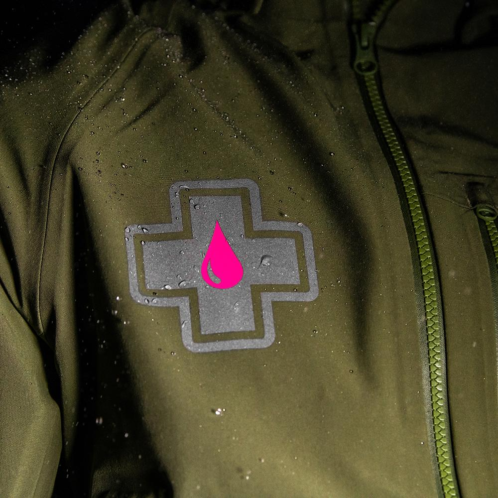 Muc-off grey and pink logo on the breast pocket in the rain