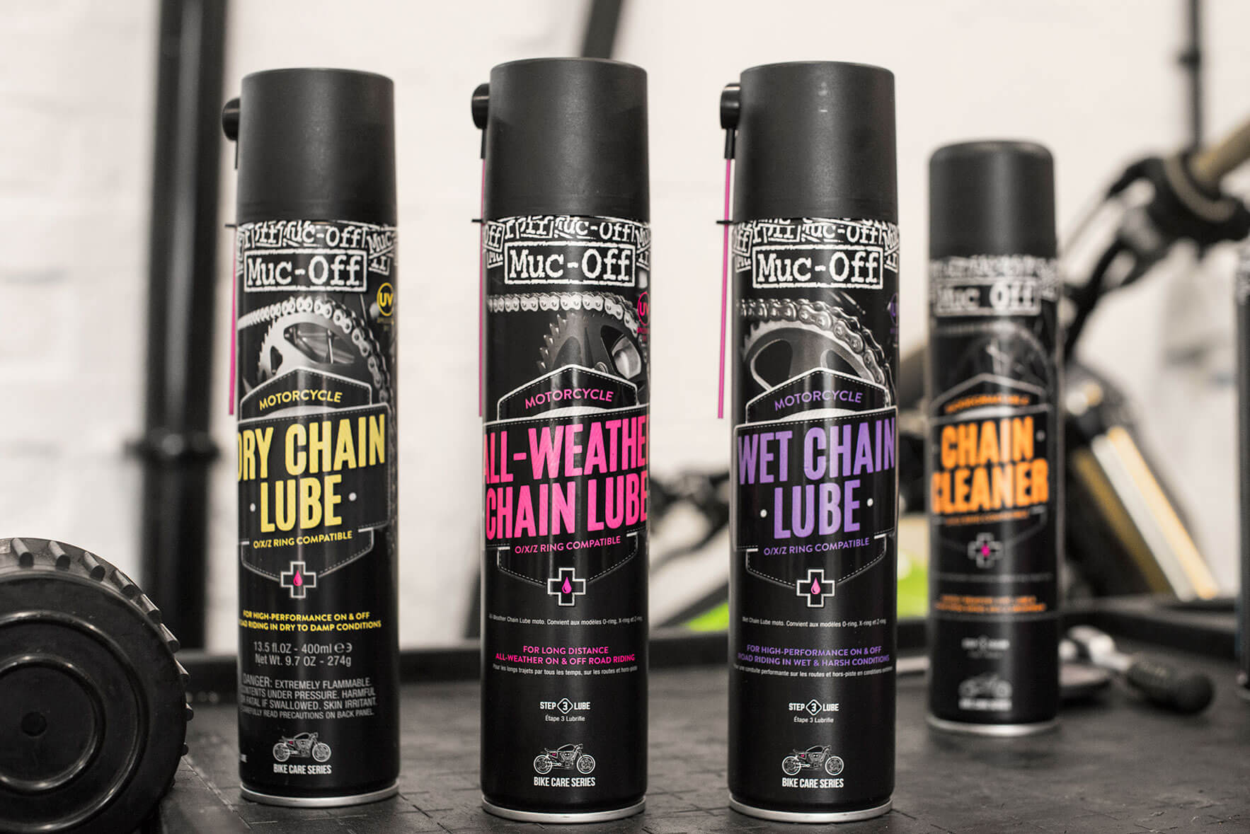 Dry chain lube can, All-Weather Chain Lube can, Wet Chain Lube can, Chain Cleaner can in mechanic setting