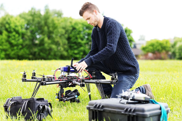 Man flying large drone in a park