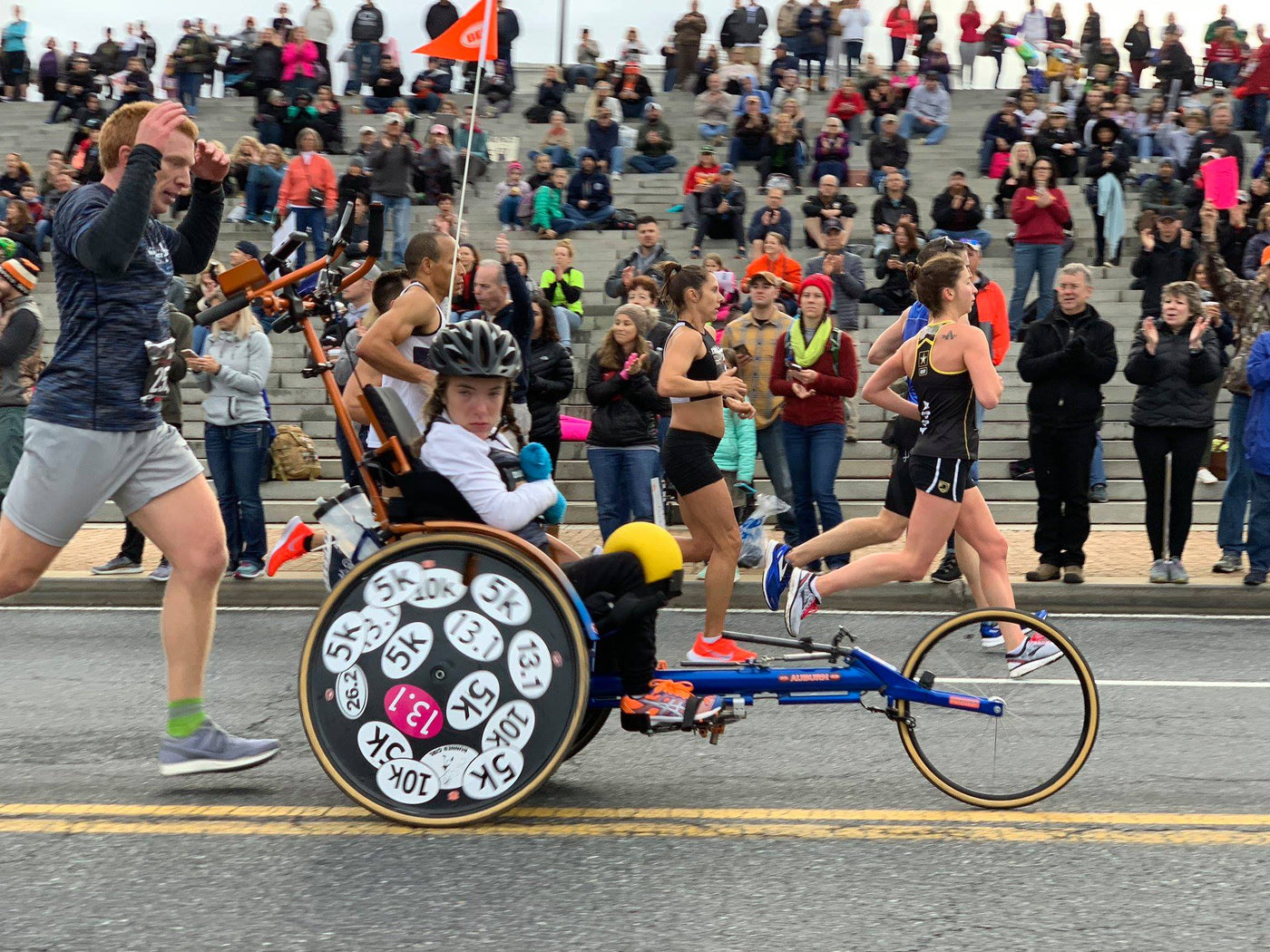 Young woman in racing chair with wheel covered in marathon stickers
