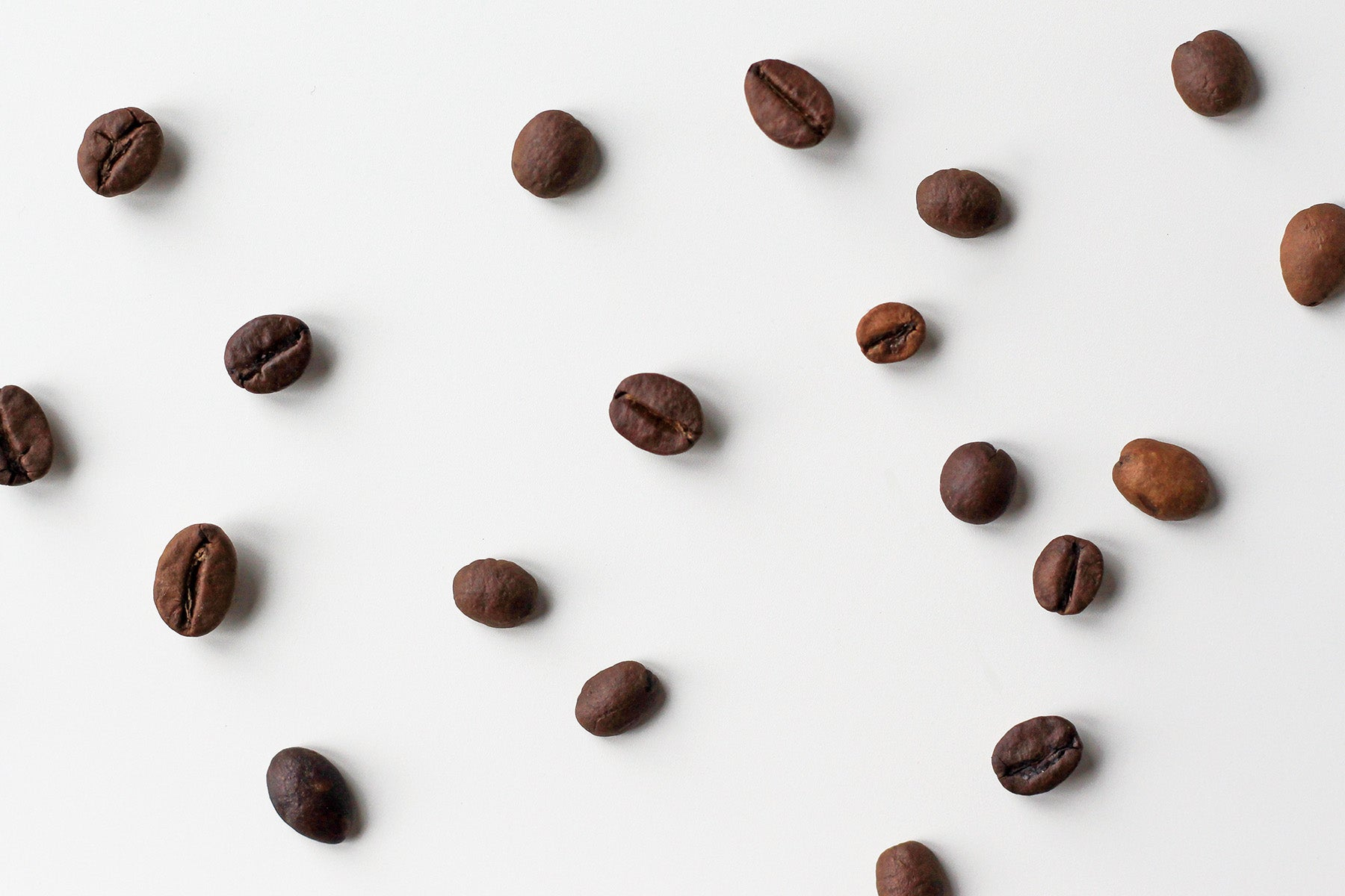 Scattered coffee beans on a plain white surface
