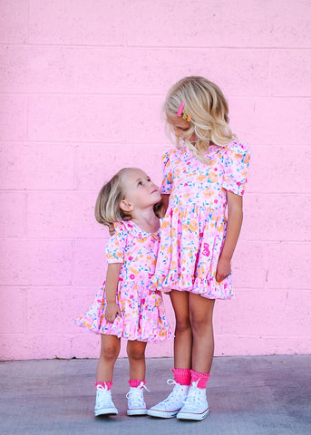 sisters in matching pink dresses
