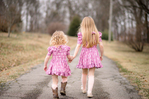 sisters walking down road in matching dresses