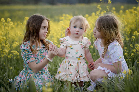 three sisters in matching floral twirl dresses