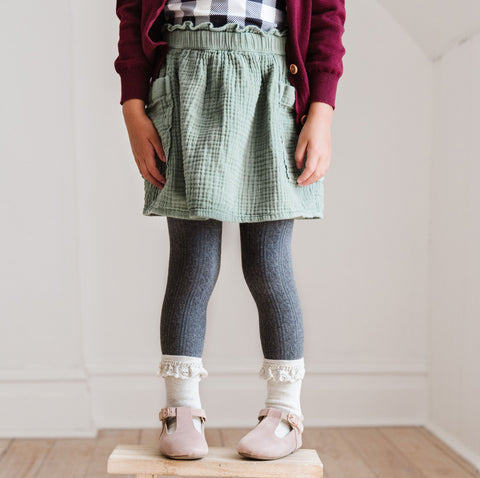 girl on stool in charcoal tights and ivory socks