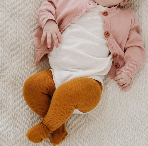 baby in onesie and mustard yellow cable knit tights