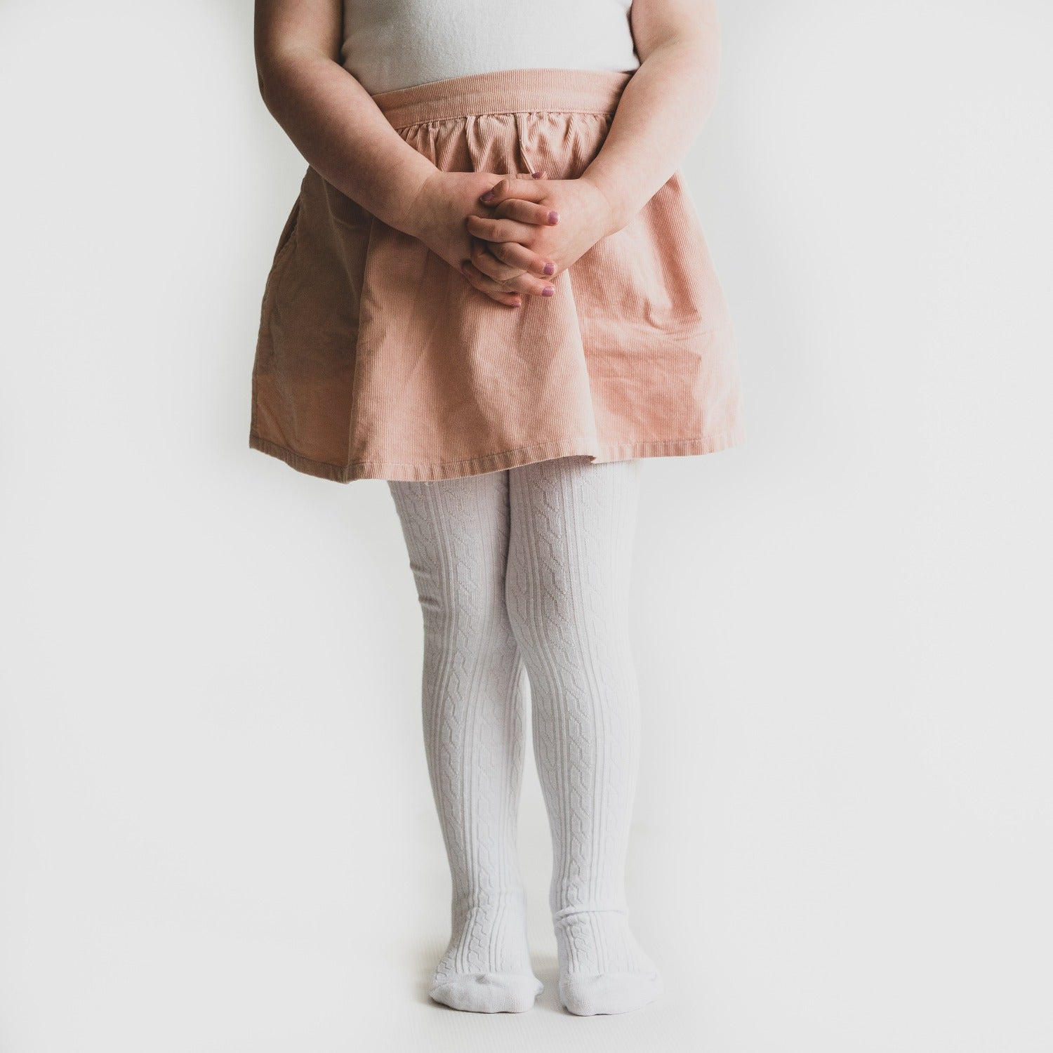 White cable knit tights on little girl with pink skirt.