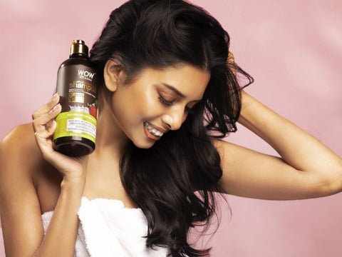 woman holding anti dandruff shampoo with glossy hair