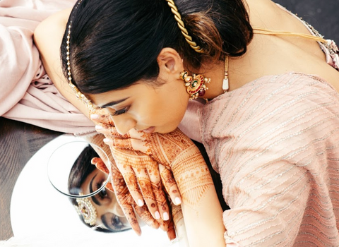 woman with henna looking at mirror