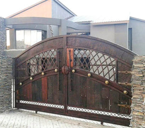 Driveway entrance sliding gate with sleeper wood paneling featuring NW/AC8 mock hinges hand painted in antique copper.