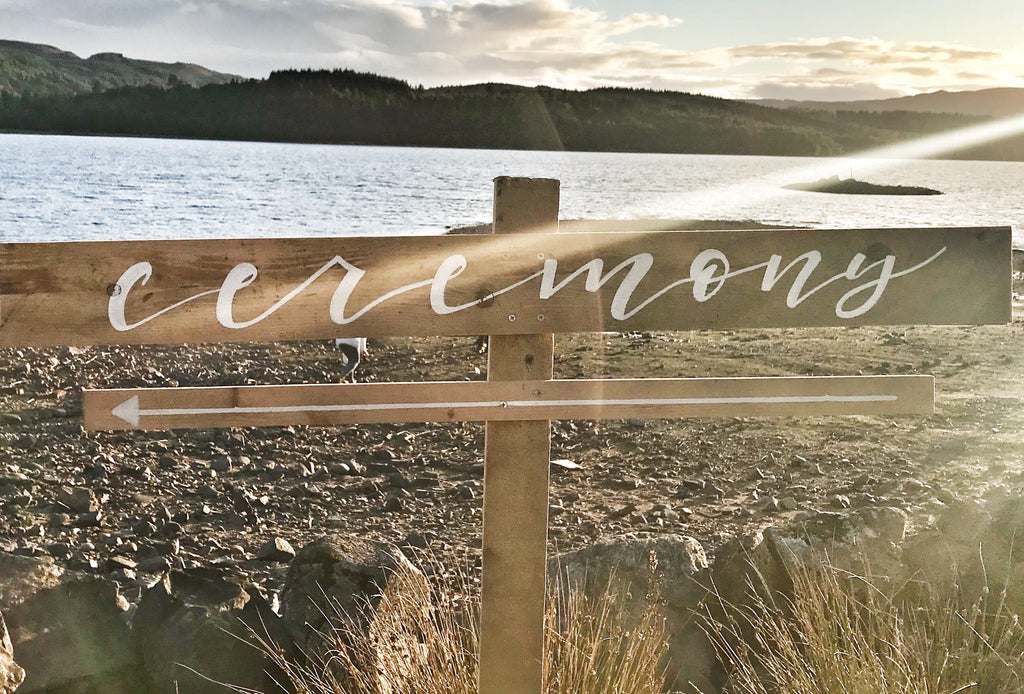 wooden post ceremony sign outdoors with white calligraphy