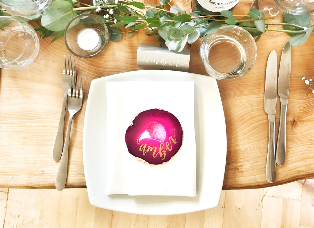 wedding table setting with large pink agate slice and gold calligraphy