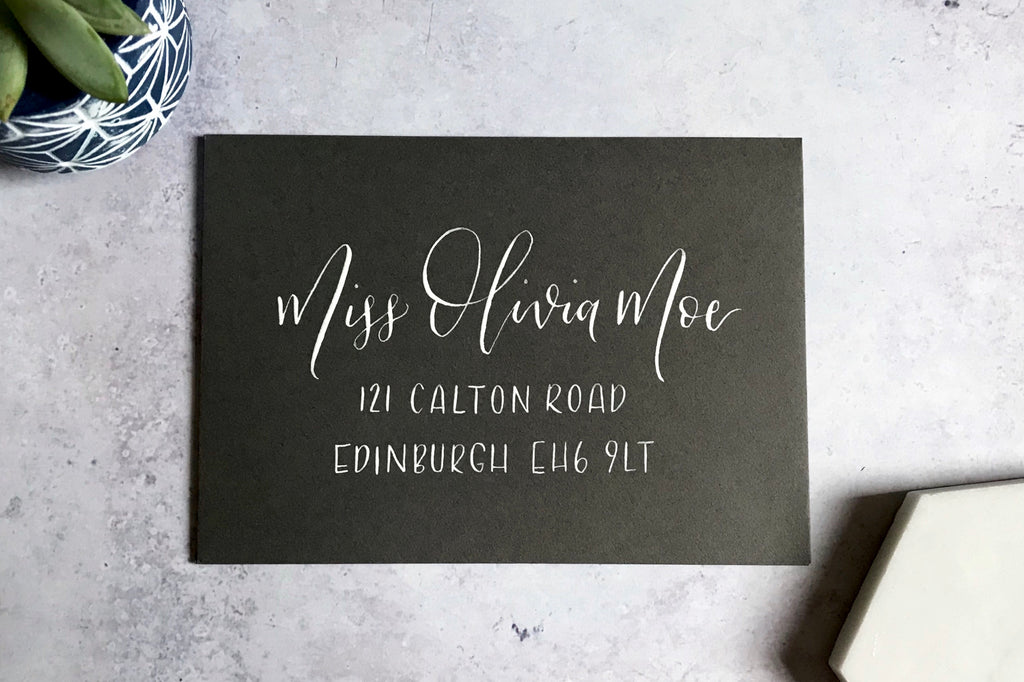 dark grey envelope with name and address written in white calligraphy