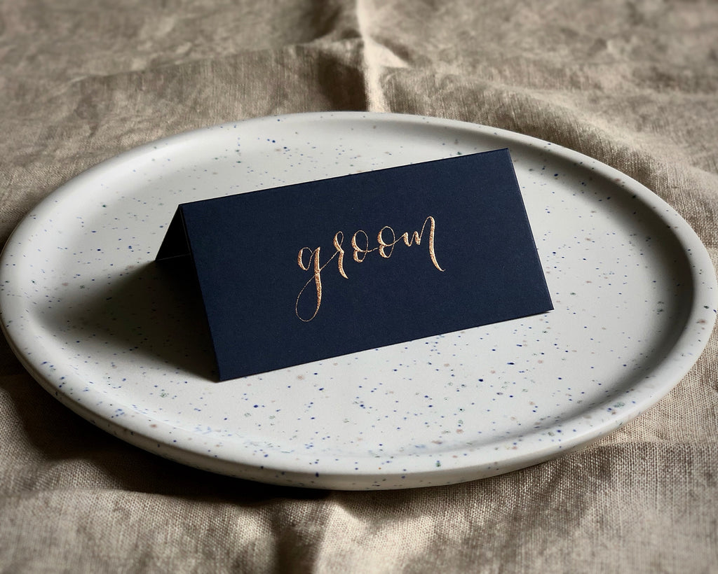 navy blue tent-fold wedding place card with copper calligraphy