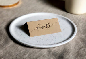 natural coloured wedding place cards with black calligraphy