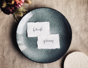 white cotton paper wedding bride and groom place cards with black calligraphy