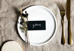 black wedding place card with white calligraphy